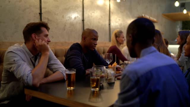 Multi-Ethnic Friends Communicating In Restaurant