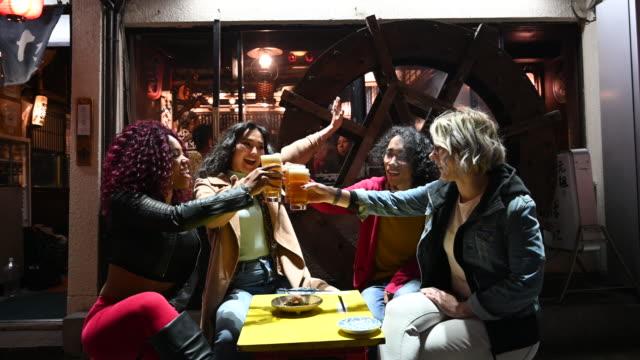 多民族の友人が日本の居酒屋で飲み物を楽しむ - 居酒屋点の映像素材/bロール