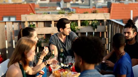 vídeos y material grabado en eventos de stock de y multiétnicas amigos disfrutando de la comida y la bebida - tejado