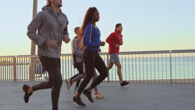 vidéos et rushes de amis multiethniques jogging sur le pont - jogging