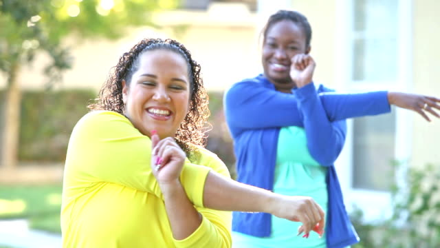 Multi-ethnic friends laughing in front yard, stretching