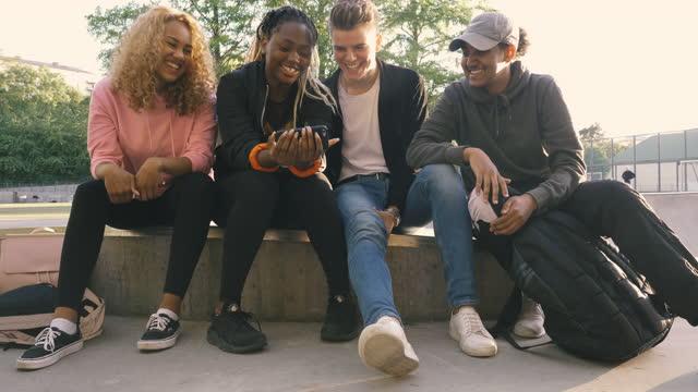 vidéos et rushes de multi-ethnic friends looking at smart phone while sitting at skateboard park - quatre personnes