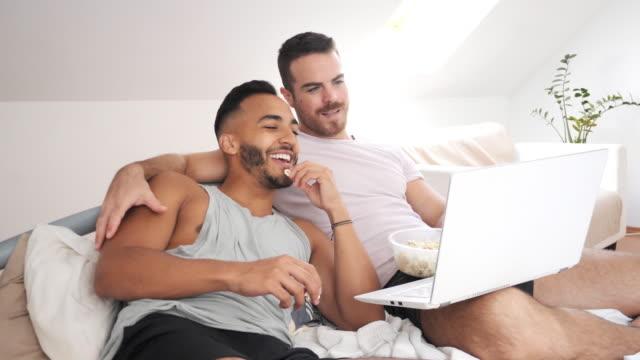 映画を見て、ポップコーンを食べるためにラップトップを使用して自宅で多民族ゲイのカップル - ゲイ点の映像素材/bロール