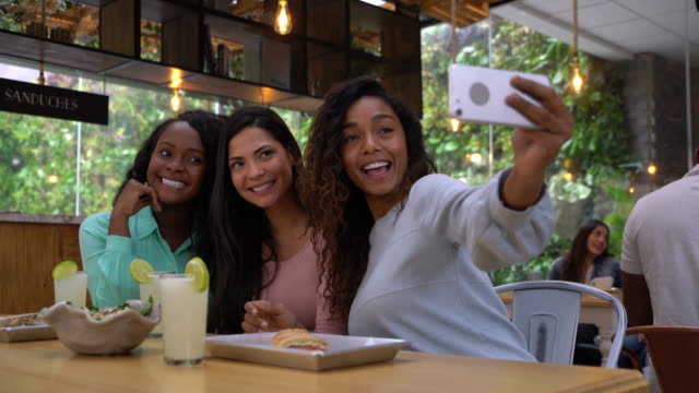 multiethnic group friends enjoying a meal at a restaurant and taking selfie with a smartphone - happy meal stock videos and b-roll footage