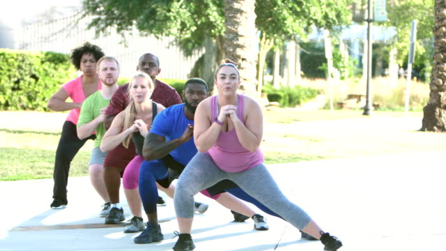 Multi-ethnic group in exercise class doing lunges