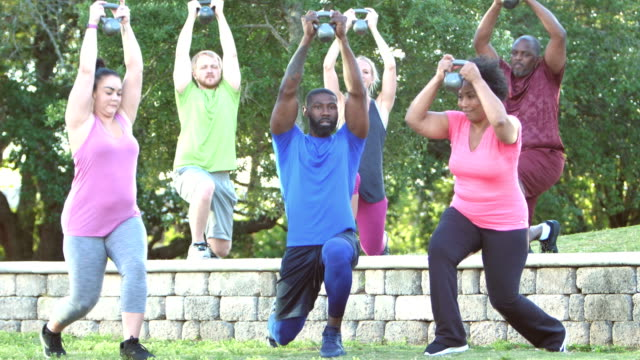 multi-ethnic group in exercise class lifting kettlebells - mid adult men stock videos & royalty-free footage