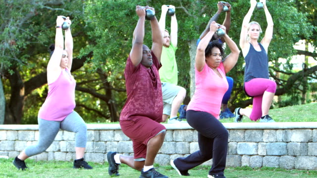 multi-ethnic group in exercise class lifting kettlebells - medium group of people stock videos & royalty-free footage