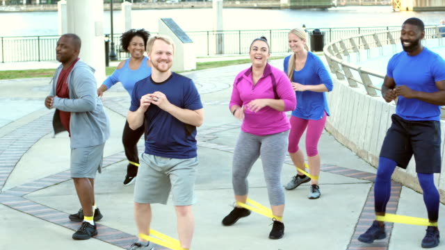 Multi-ethnic group in exercise class, resistance bands