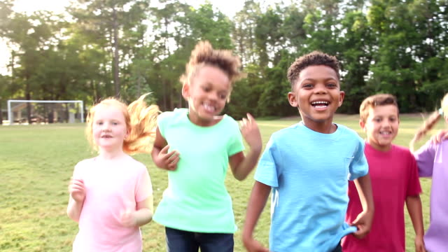 multi-ethnic group of boys and girls jumping in park - 6 7 years stock videos & royalty-free footage