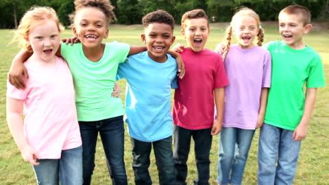 vidéos et rushes de groupe multi-ethnique de garçons et de filles criant dans le parc - public park