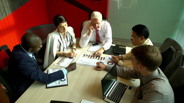 分析グラフやビジネス ドキュメントの実業家の多民族のグループ。テーブルの上のグラフ ドキュメント。 - 忙しい点の映像素材/bロール