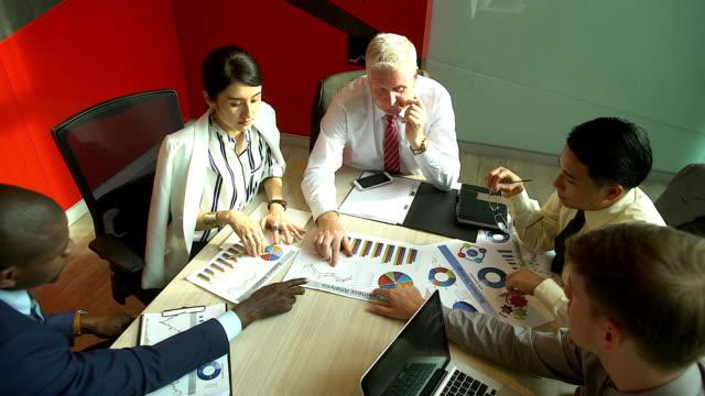 分析グラフやビジネス ドキュメントの実業家の多民族のグループ。テーブルの上のグラフ ドキュメント。 - 会議点の映像素材/bロール