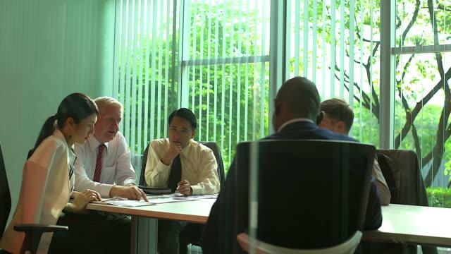 vídeos y material grabado en eventos de stock de grupo multiétnico de empresarios analizando gráficos y documentos de negocios. documento gráfico sobre la mesa. - asia sudoriental