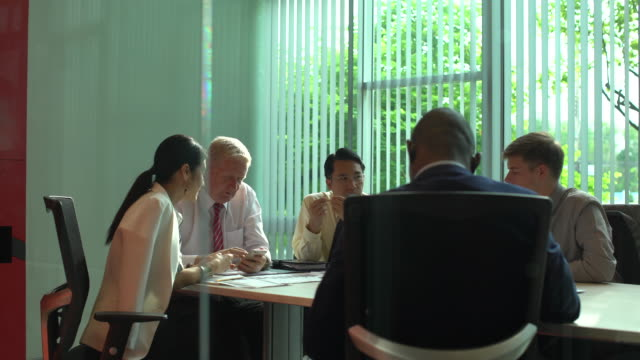 multi-ethnic group of businesspeople analyzing graphs and business document.graph document on the table. - business strategy stock videos & royalty-free footage