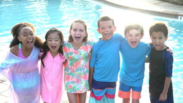 multietnisk grupp barn av poolen - tre fjärdedels längd bildbanksvideor och videomaterial från bakom kulisserna