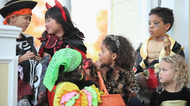 MS PAN Multi-ethnic group of children dressed in Halloween costumes, eating candy sitting on porch / Richmond, Virginia, USA
