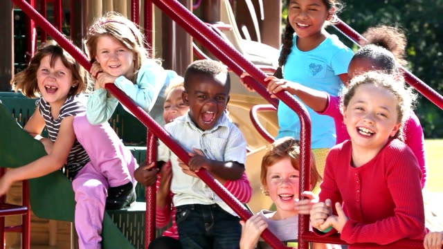multi-ethnic group of children laughing on playground - mixed age range stock videos & royalty-free footage