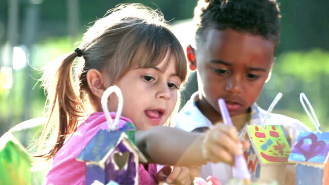 multi-ethnic group of children painting birdhouses - primary age child stock videos and b-roll footage