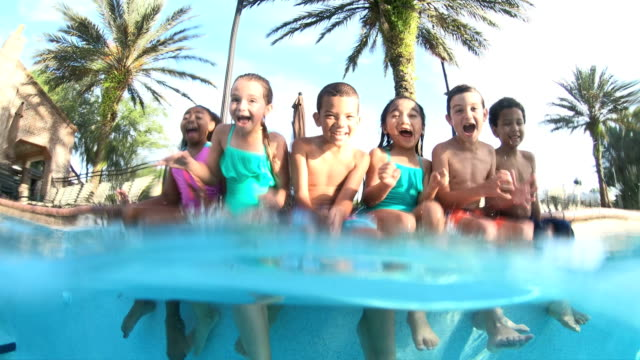 vídeos y material grabado en eventos de stock de grupo multiétnico de niños sentados con los pies en la piscina - saludar con la mano