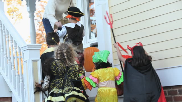 MS TU TD Multi-ethnic group of children trick or tricking on Halloween / Richmond, Virginia, USA
