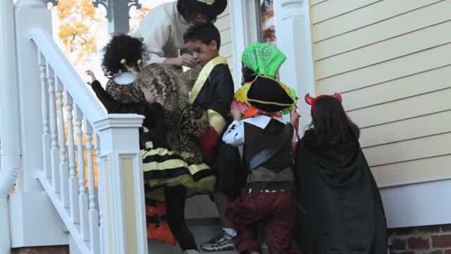 ms tu td pan multi-ethnic group of children trick or tricking on halloween / richmond, virginia, usa - 扮装点の映像素材/bロール