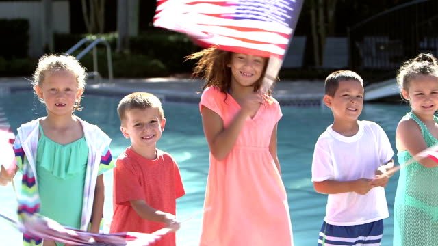 Multi-ethnic group of children waving American flags