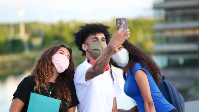multi-ethnic group of college students taking a selfie while wearing masks - back to school stock videos & royalty-free footage