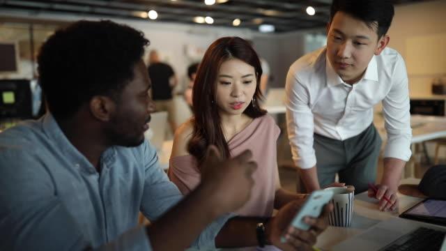 multietnisk grupp av medarbetare som använder smart telefon - medarbetarengagemang bildbanksvideor och videomaterial från bakom kulisserna