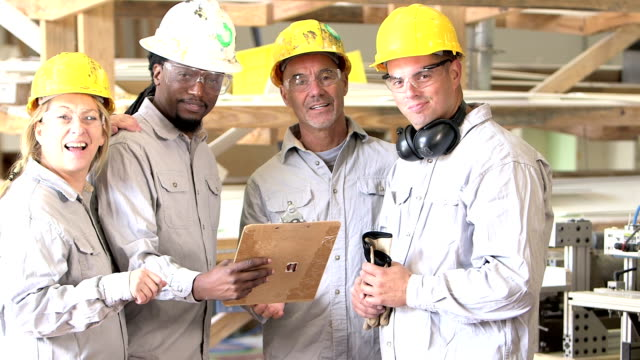 multi-ethnic group of factory workers with clipboard - operatore edile video stock e b–roll