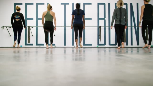 a multi-ethnic group of five women in their twenties walk to a ballet barre and start stretching in an exercise studio - barre stock videos & royalty-free footage