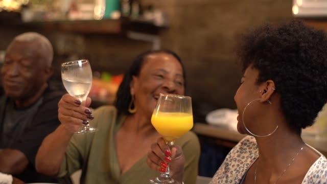 vídeos de stock, filmes e b-roll de multi-étnica grupo de amigos e família no brinde de comemoração em um jantar - avó