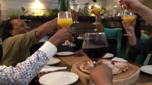 vídeos de stock, filmes e b-roll de multi-étnica grupo de amigos e família no brinde de comemoração em um jantar - copo