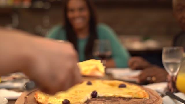 vídeos y material grabado en eventos de stock de grupo multiétnico de amigos y familiares comiendo pizza en casa - comida no saludable