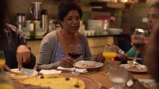 vídeos de stock, filmes e b-roll de multi-étnica grupo de amigos e família para comer pizza em casa - almoço