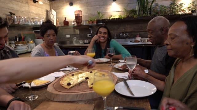 vídeos de stock, filmes e b-roll de multi-étnica grupo de amigos e família para comer pizza em casa - latino americano