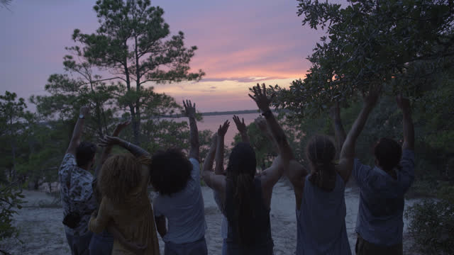 a multi-ethnic group of friends raise their arms while enjoying the sunset over the ocean - hippy stock videos & royalty-free footage