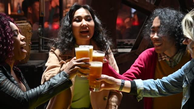 友人の多民族グループは一緒にビールのグラスを乾杯 - 居酒屋点の映像素材/bロール