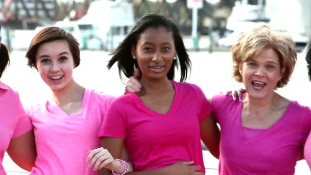 multi-ethnischen gruppe von glücklichen frauen tragen rosa, in einer reihe - multi ethnic group stock-videos und b-roll-filmmaterial