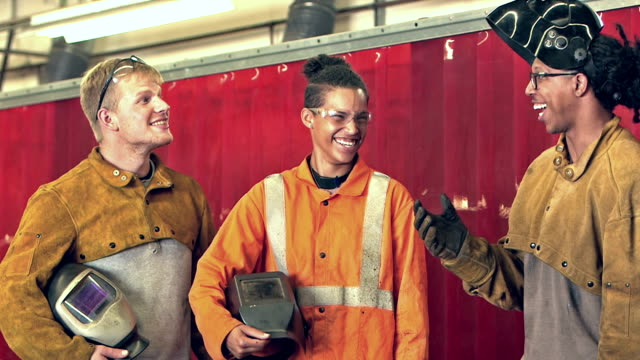 Multi-ethnic group of metal workers talking, laughing