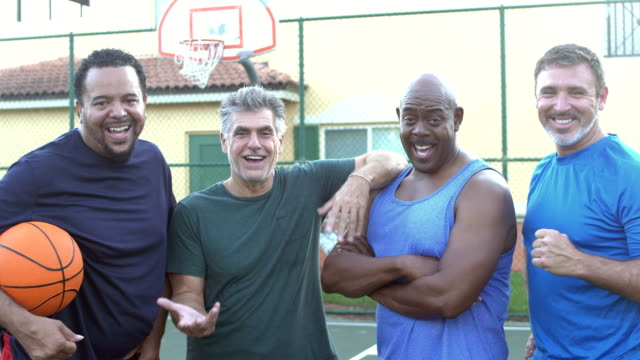 multi-ethnic group of middle aged men playing basketball - male friendship stock videos and b-roll footage