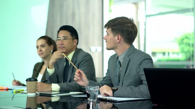 multi-ethnischen gruppe von menschen aufmerksam geschäftsleute in meeting im büro. - tischflächen aufnahme stock-videos und b-roll-filmmaterial