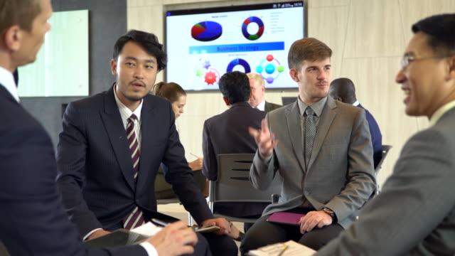 セミナー ルームをブレーンストーミングの人親切なビジネスマンの多民族のグループ。 - 高精細点の映像素材/bロール