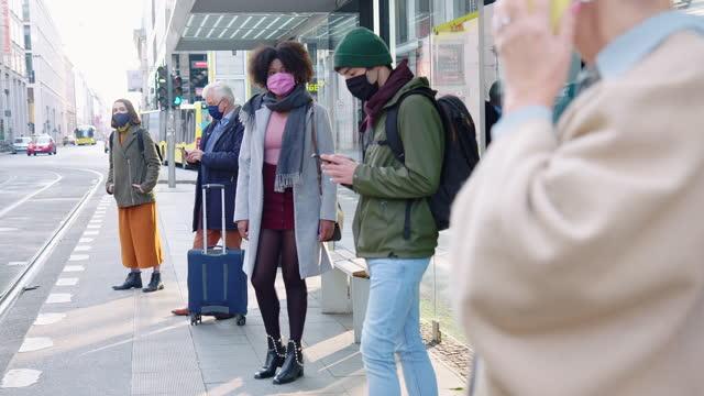 multiethnische gruppe von menschen, die an der straßenbahnhaltestelle warten - bus stock-videos und b-roll-filmmaterial