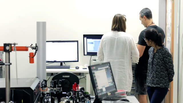 Multi-ethnic Group of Researchers Working in Laboratory with High Frequency Laser