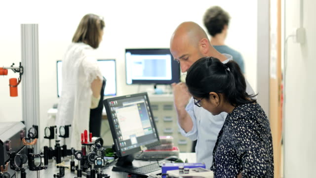 Multi-ethnic Group of Researchers Working in Laboratory with Powerful High Frequency Laser