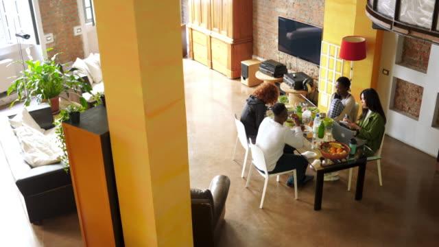 vídeos de stock, filmes e b-roll de grupo multiétnico de companheiros de quarto que compartilham do apartamento - sala de jantar