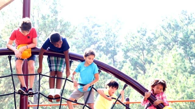 vídeos y material grabado en eventos de stock de grupo multiétnico de niños jugando en el patio de la escuela. - estructura metálica para niños
