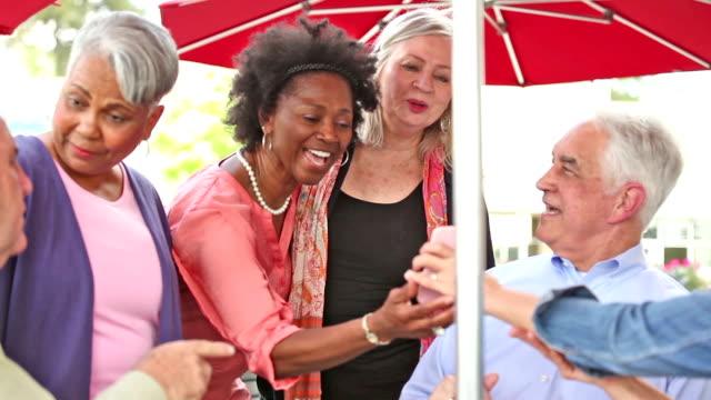 Multi-etnische groep senior volwassen vrienden genieten van een bezoek op outdoor cafe.