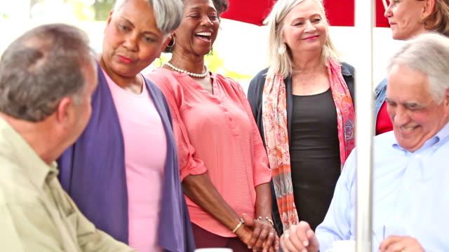 stockvideo's en b-roll-footage met multi-etnische groep senior volwassen vrienden genieten van een bezoek op outdoor cafe. - jong van hart