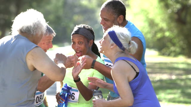 Multi-ethnic group of seniors, high-fives after race